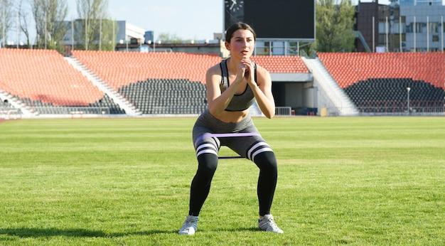 Het mooie atletische meisje hurkt op het gras in het stadion