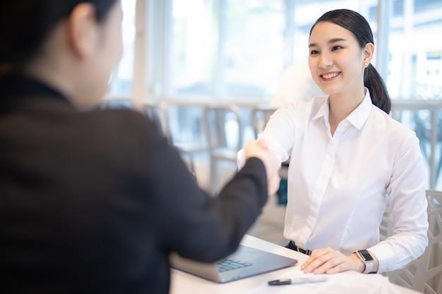 Het mooie aziatische bedrijfsvrouw schudden dient het moderne bureau van het stadswerk in.