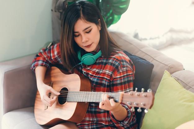 Het mooie aziatische jonge hipstermeisje het spelen gitaar thuis voor ontspant