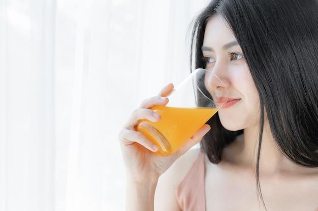 Het mooie aziatische leuke meisje van de schoonheidsvrouw voelt gelukkig het drinken jus d'orange voor goede gezondheid in de ochtend