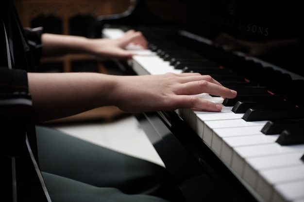 Het mooie aziatische meisje leert piano spelen.