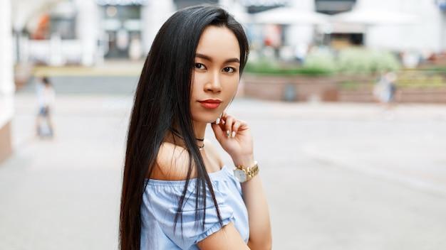 Het mooie aziatische vrouw stellen in de stad.