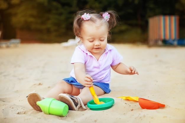 Het mooie baby spelen in het zandbakspeelgoed. kindertijd en ontwikkeling.