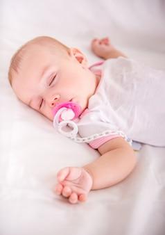 Het mooie babymeisje slaapt in haar bed.