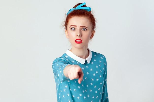 Het mooie blanke meisje, gekleed in een blauwe jurk, wijd open mond, verraste geschokte blikken, wijzende vinger naar de camera. selectieve aandacht. geïsoleerde studio-opname op grijze achtergrond