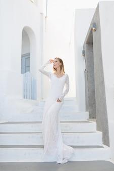 Het mooie blonde haar jonge vrouwen bruid blauw in een bruiloft witte lange sexy jurk op santorini in griekenland