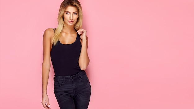 Het mooie blonde jonge model stellen op roze