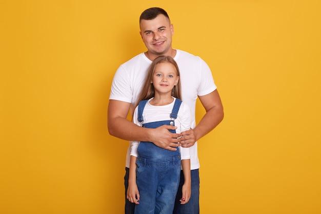 Het mooie blonde meisje dat wit overhemd en overall draagt, zich dichtbij haar vader bevindt, drukt liefde en zorg uit, glimlachend knap mensen wit t-shirt