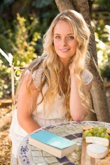 Het mooie blonde ontspannen met een boek en voedsel in de tuin