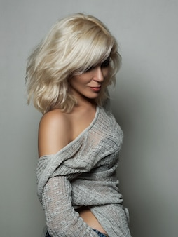 Het mooie blonde vrouw stellen over grijze muur