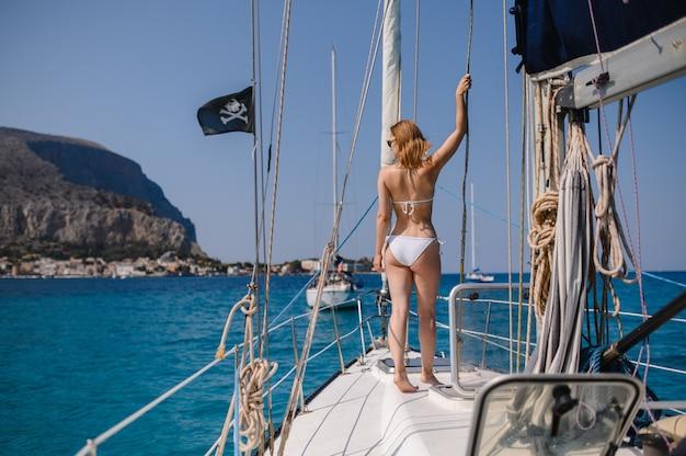 Het mooie blondemeisje draagt manierzwempak die de zomerreis op een jacht doen.