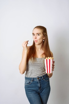 Het mooie blondemeisje eet popcorn en let op comedia film die op witte muur wordt geïsoleerd. kopieer space, sjabloon voor blog en reclame. vrouw houdt pop corn