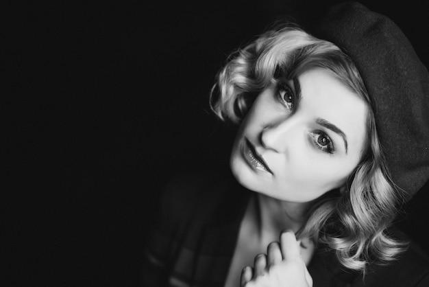 Het mooie blondemeisje in een baret bekijkt de camera in retro zwart-witte stijl