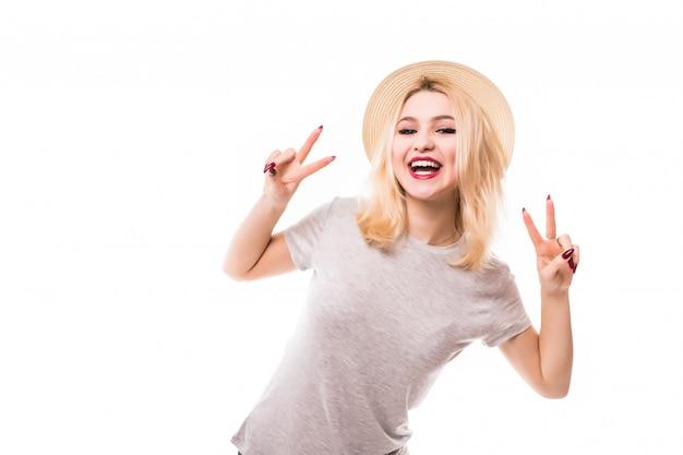Het mooie blondemeisje in hoed toont vrede op beide handen