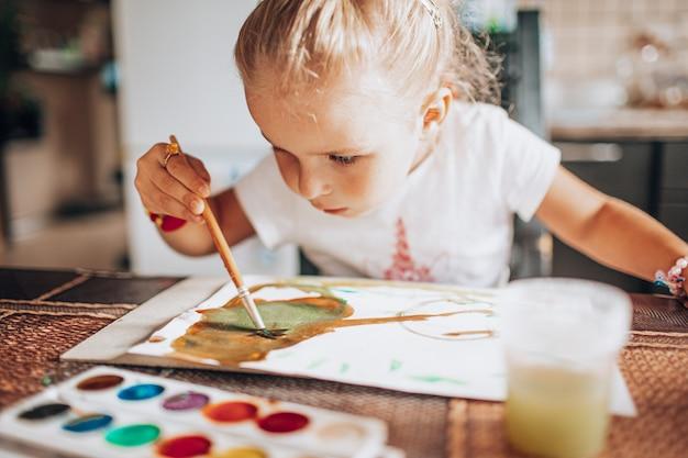 Het mooie blondemeisje schilderen met penseel en waterkleuren in de keuken. kid activiteiten concept. detailopname. afgezwakt