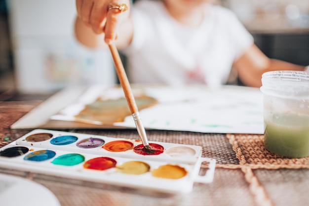 Het mooie blondemeisje schilderen met penseel en waterkleuren in de keuken.