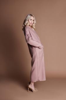Het mooie blondevrouw stellen in een roze laag op een beige achtergrond. modeshow kleding