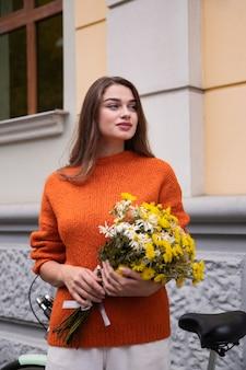 Het mooie boeket van de vrouwenholding van bloemen naast fiets