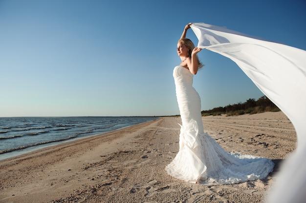 Het mooie bruid stellen bij een overzeese kust
