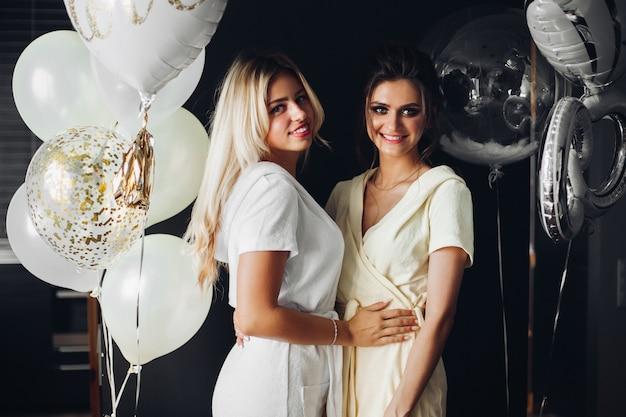 Het mooie bruid stellen met bruidsmeisje dichtbij ballons