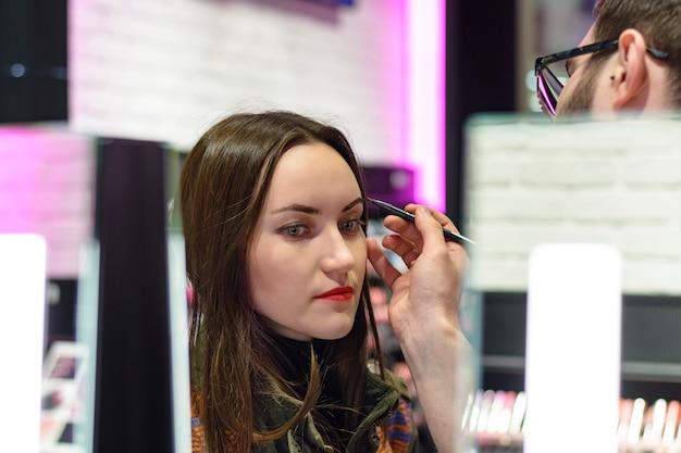 Het mooie brunette met rode lippenstift test de oogschaduw in schoonheidswinkel