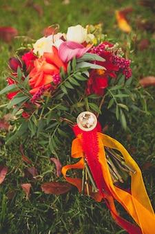 Het mooie de herfst bruids boeket ligt op het gras.