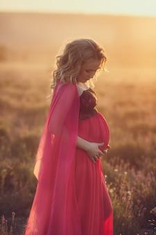 Het mooie de zwangere vrouw van de provence ontspannen op lavendelgebied het letten op op de mand van de zonsondergangholding met lavandabloemen. serie. verleidelijk meisje met paarse lavendel. blonde dame in bloesem veld