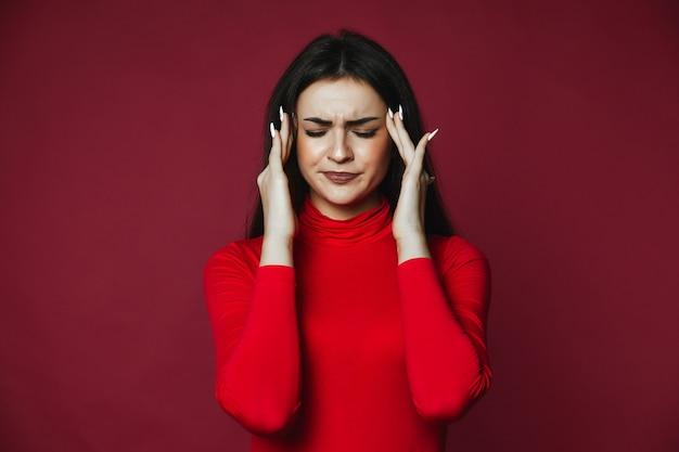 Het mooie donkerbruine kaukasische meisje kleedde zich in rode trui met pijnlijke hoofdpijn