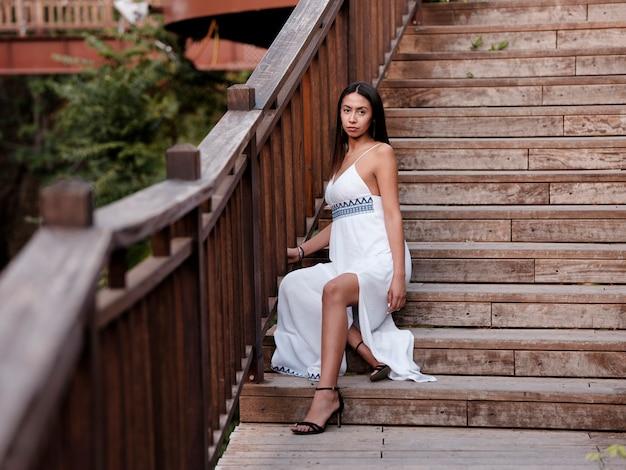 Het mooie donkerbruine meisje in een witte kleding zit op houten treden bij het park