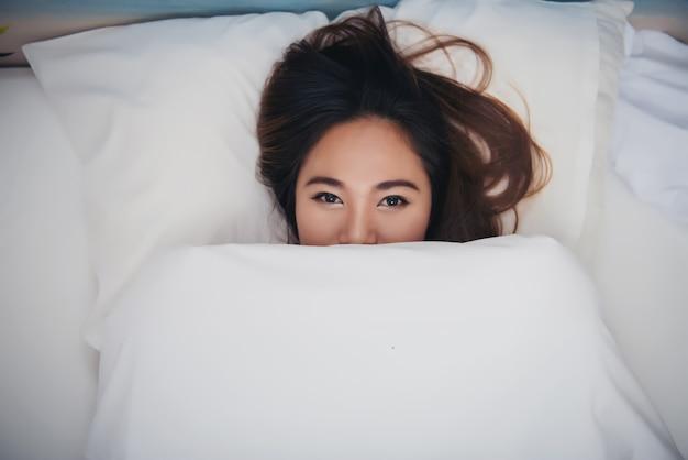 Het mooie donkerbruine meisje ligt op bed