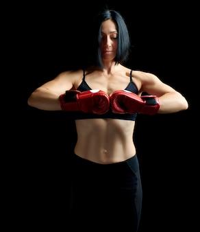 Het mooie donkerbruine sportief ogende meisje in een zwarte bustehouder en beenkappen bevindt zich op een donkere achtergrond