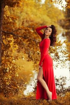 Het mooie donkerbruine vrouw stellen in een luxueuze lange rode kleding die zich in het bos van de de herfstberk bevinden.