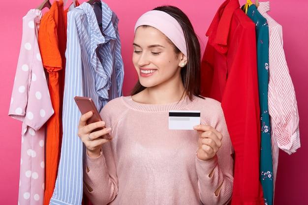 Het mooie donkerharige jonge wijfje met vrolijke uitdrukking, houdt slimme telefoon en creditcard. gelukkig meisje voert online betaling uit. vrouw kiest outfits in online shop. betaling en winkelen concept.