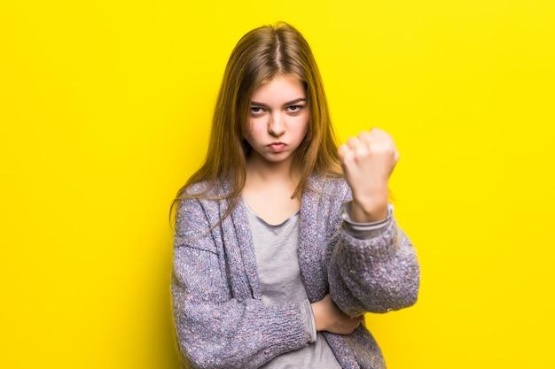 Het mooie droevige jonge close-up van het tienermeisje bedreigt vuist