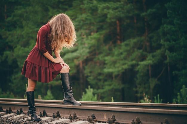 Het mooie droevige meisje verbergt gezicht door haar. humeurige dame in de kleding van bourgondië in bos op spoorweg. gedeprimeerd eenzaam meisje op spoorweg bij dageraad. zon in krullend natuurlijk haar in de herfst. slecht humeur. beledigd meisje.