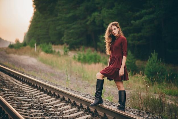 Het mooie dromerige meisje met krullend natuurlijk haar geniet van aard in bos op spoorweg.