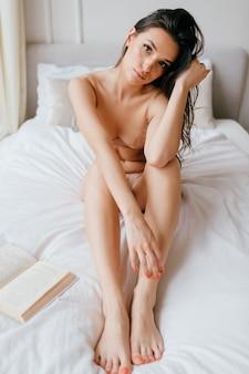 Het mooie elegante meisje stellen in bed met boek