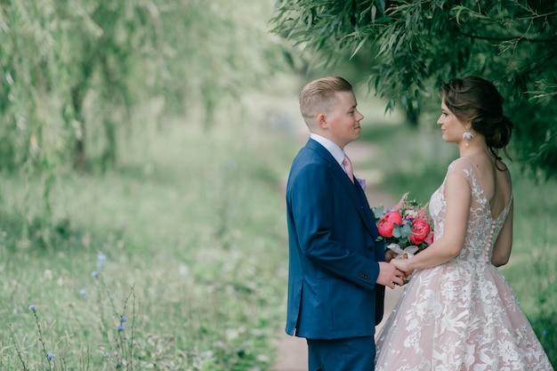 Het mooie en jonge openluchtportret van het huwelijkspaar