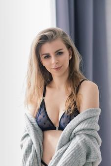 Het mooie en jonge vrouw stellen in zwarte sexy lingerie.
