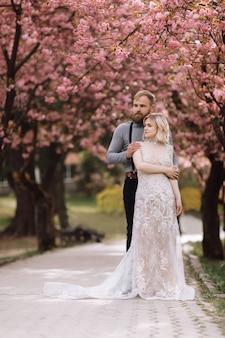 Het mooie en leuke paar in tot bloei komende roze kers of sakuratuin, omhelst de gebaarde man vrouw in luxekleding op een zonnige dag. lente bruiloft portret.