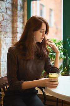 Het mooie ernstige modieuze modieuze slimme meisje zit bij het venster in koffie en het drinken van gezonde gele smoothie