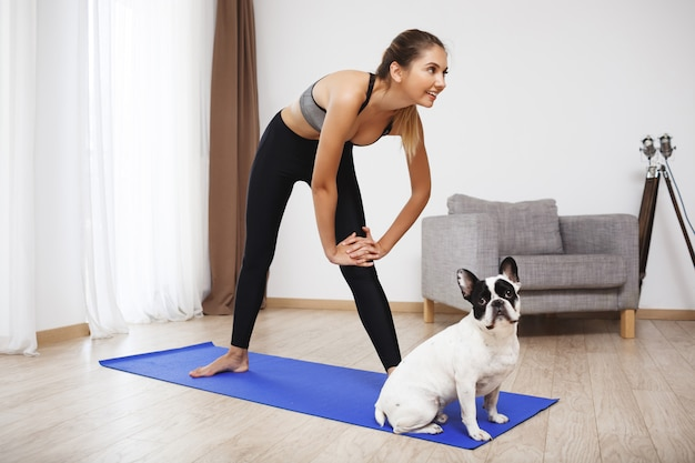 Het mooie fitness meisje maakt sportoefeningen met hond