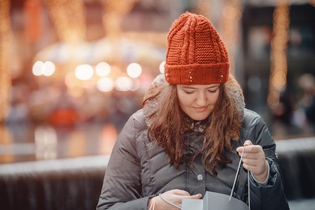 Het mooie gelukkige meisje gaat met papieren zakken winkelen na het winkelen in de stad.