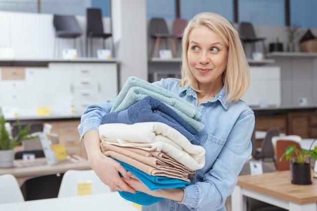Het mooie gelukkige vrouw glimlachen, die opgewekt weg kijken, die stapel nieuwe handdoeken houden koopt zij bij meubilairopslag
