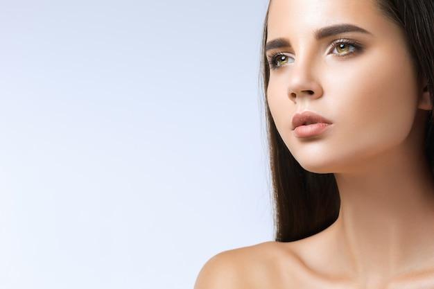 Het mooie gezicht van een jonge vrouw met een schone, frisse huid