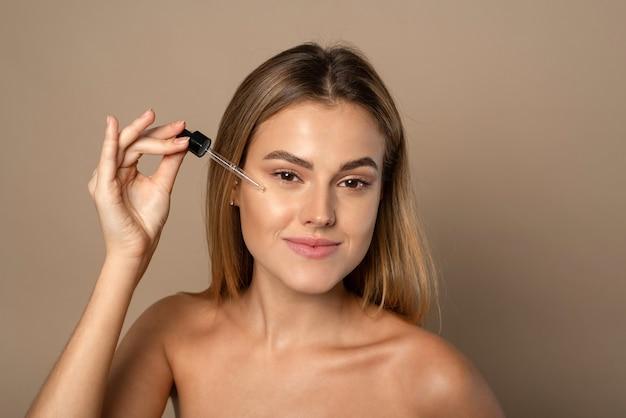 Het mooie gezichtsportret van jonge vrouw past gezichtsserum op een wang toe.