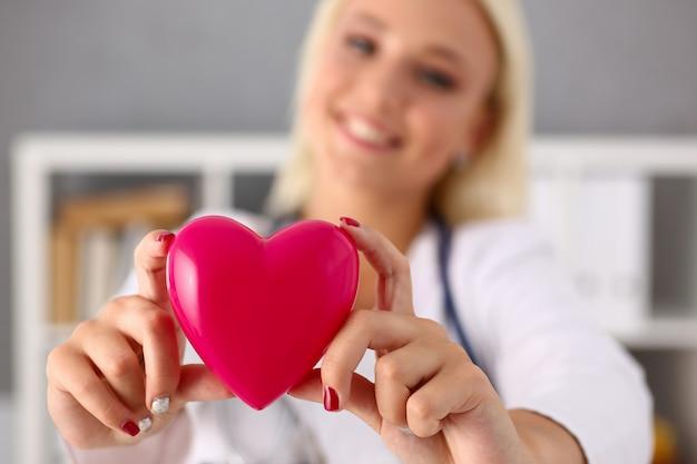 Het mooie glimlachende blonde vrouwelijke hart van de artsengreep