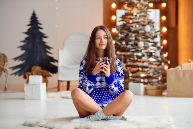 Het mooie glimlachende meisje in warme nieuwjaarsweater zit op een warm wit tapijt
