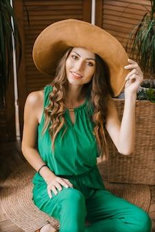 Het mooie glimlachende meisje met heldere make-up in een groene jumpsuit in een hoed met een brede rand zit en houdt zijn hand op de hoed