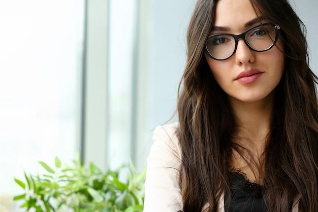 Het mooie glimlachende meisje op werkplaats kijkt in camera portret